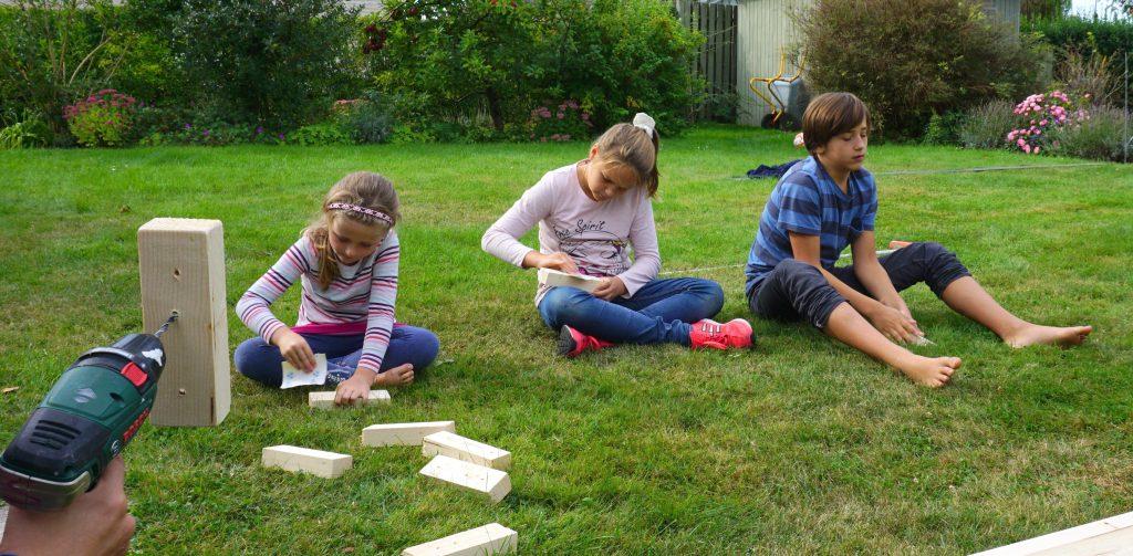 børn laver højbed i træ